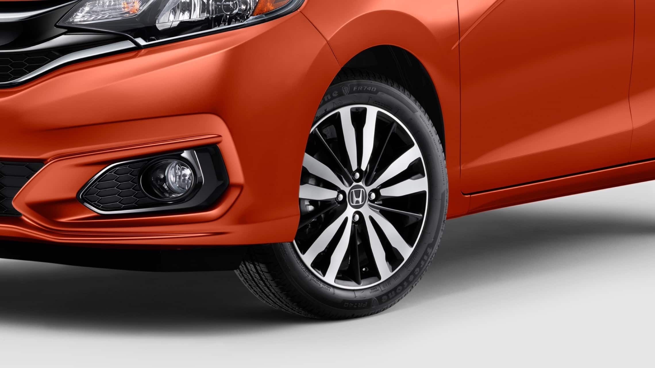 Front driver-side view of 16-inch alloy wheel detail on the 2020 Honda Fit EX-L in Orange Fury.