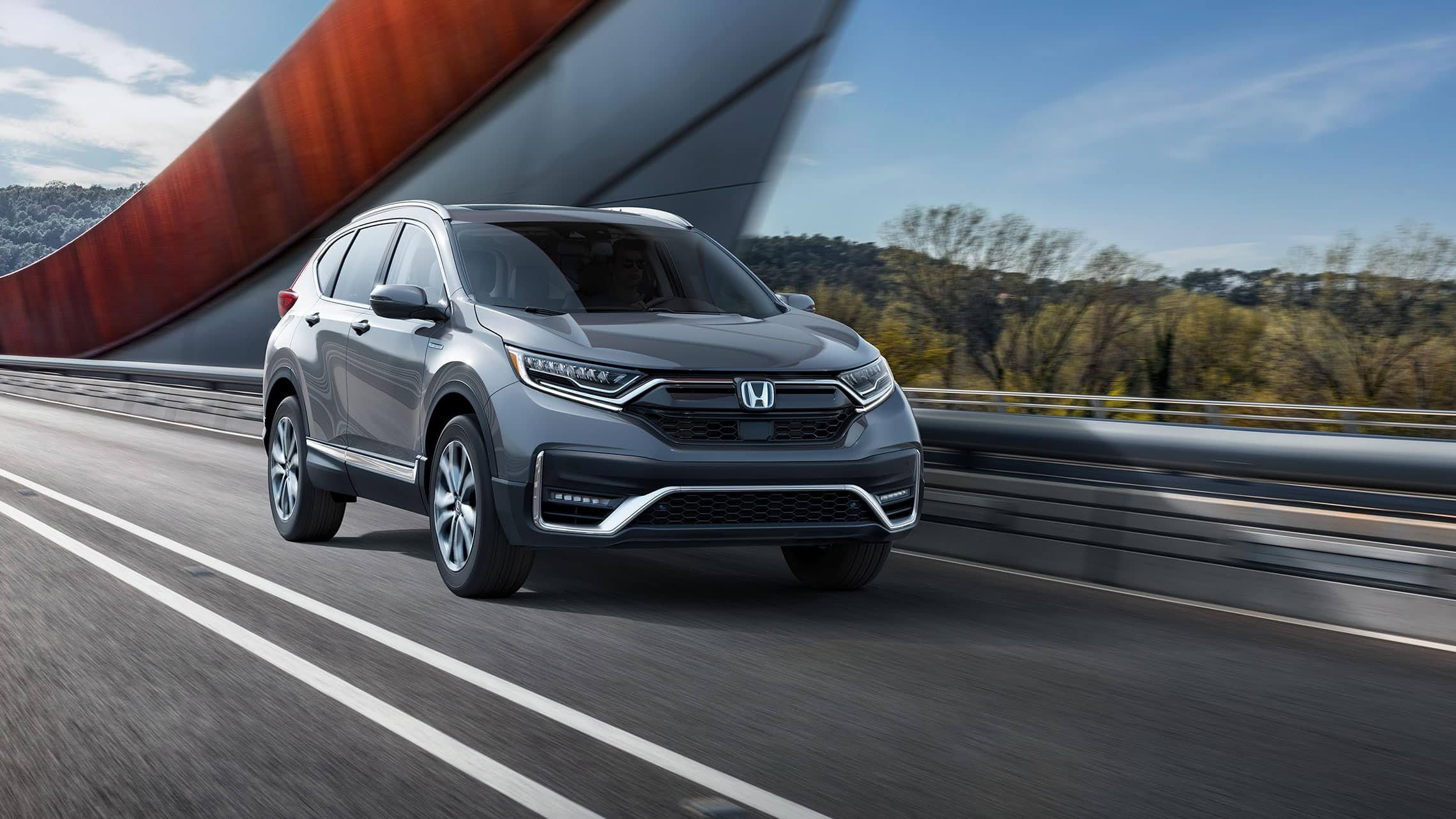 Front passenger-side view of the 2021 CR-V Hybrid Touring in Modern Steel Metallic, driving across a bridge.