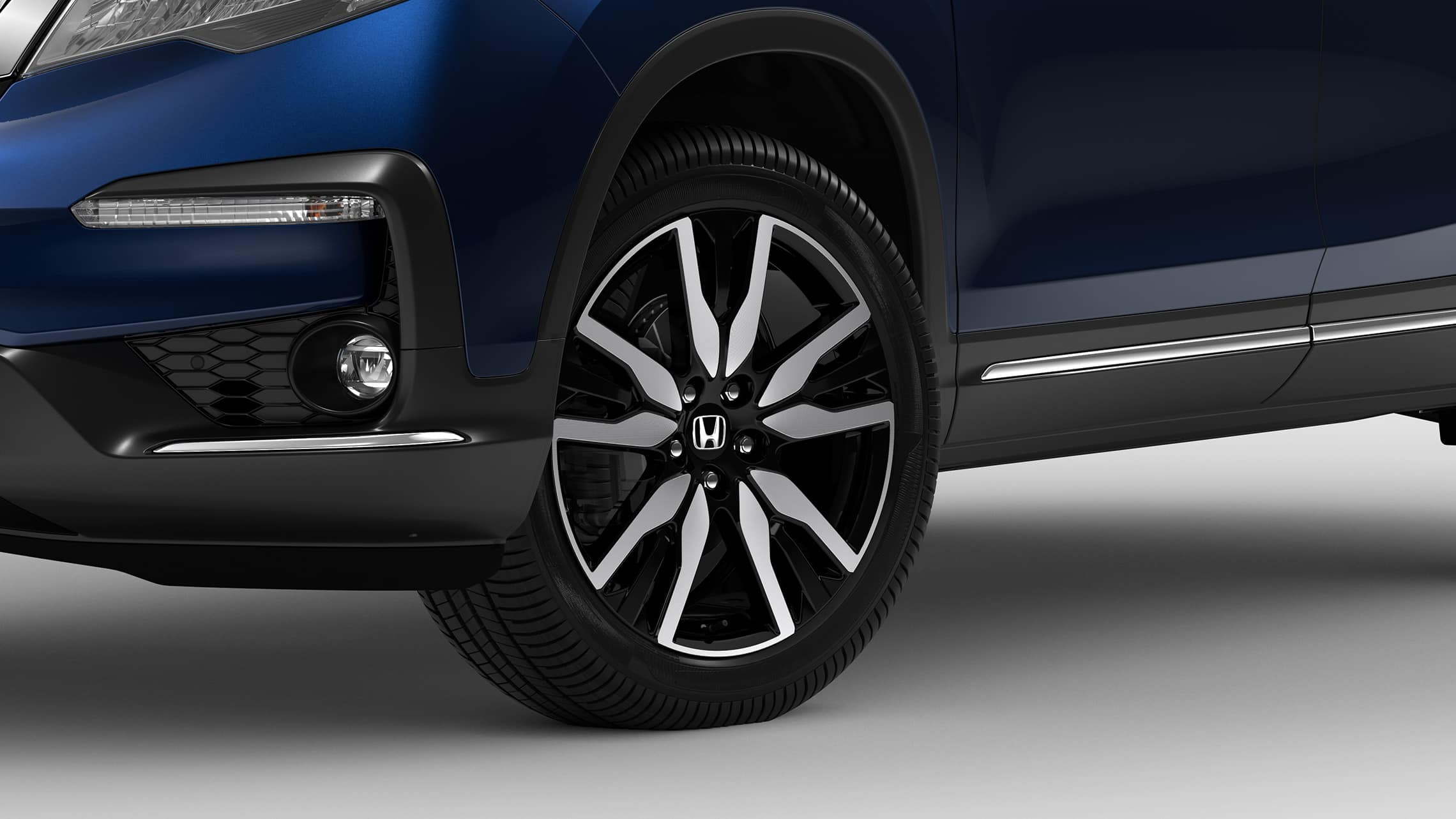 Front 3/4 driver's side close-up view of 20-Inch Alloy wheel and tire detail on 2021 Honda Pilot Elite in Obsidian Blue Pearl.